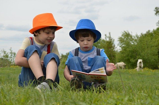 2 small boys reading a book